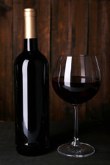 Red wine glass and bottle of wine on wooden background