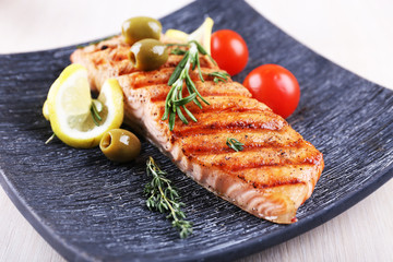 Grilled salmon and vegetables on plate on wooden background