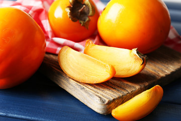 Ripe persimmons on cutting board, on color wooden background