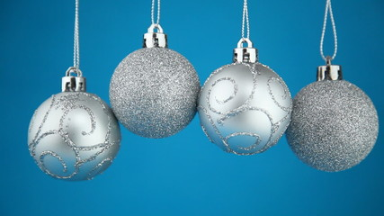 Four Christmas balls slowly shake on a blue background