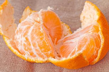 Disassembled tangerine close-up on sacking