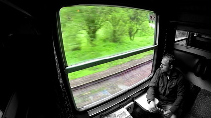 Business traveller looks through the window during train trip.
