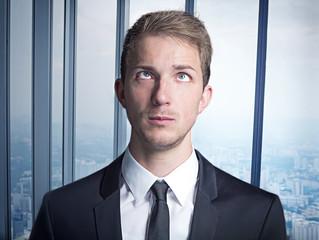 junger Geschäftsmann im anzug blickt auf die stirn