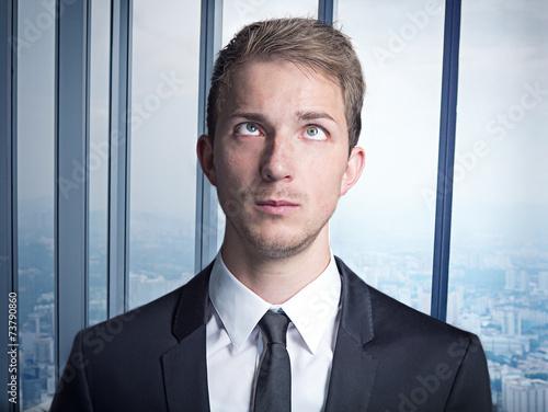 canvas print picture junger Geschäftsmann im anzug blickt auf die stirn