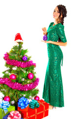Beautiful young woman near a Christmas tree with many gifts