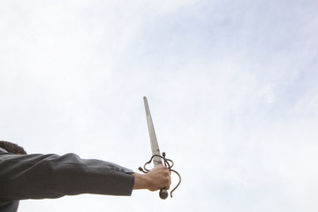 A business man in a suit holding a sword high in the sky