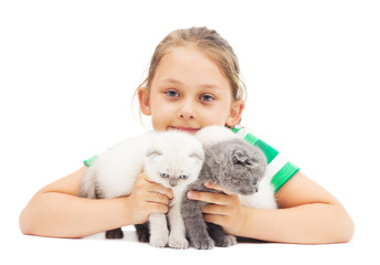 kid embraces three British lop-eared kitten on a white backgroun
