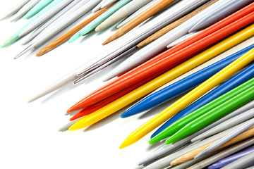 Tips of Multicolored Plastic Knitting Needles on White