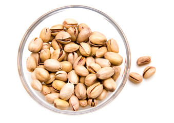 Pistachios on glass bowl on a white background seen from above