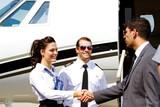 Stewardess and pilot greeting passenger