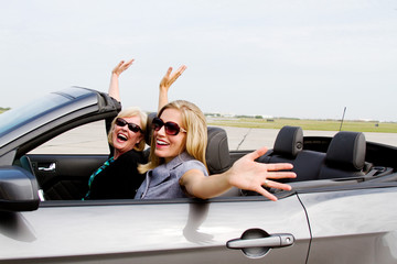 Two women with arms up in convertible