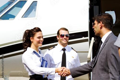 Leinwanddruck Bild Stewardess and pilot greeting passenger