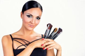 Smiling black woman girl holding makeup brushes.