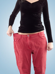 Woman shows her weight loss by wearing an old big trousers.