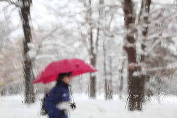Blurry and snowy man with umbrella