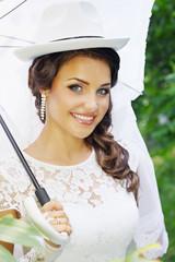 bride in a hat with umbrella
