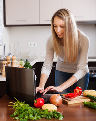 woman using notebook during cooking vegetables