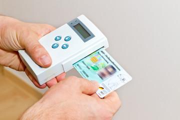 Hausarzt mit Kartenlesegerät beim Hausbesuch