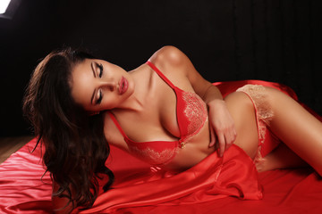 sexy girl with dark hair in red lingerie lying on silk sheet