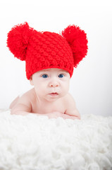 Newborn baby in red hat looking into the camera