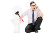 Angry man sitting by a toilet and talking on phone