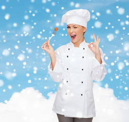 smiling female chef with fork showing ok sign
