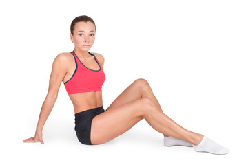 Beautiful fitness woman with perfect body sitting. Isolated