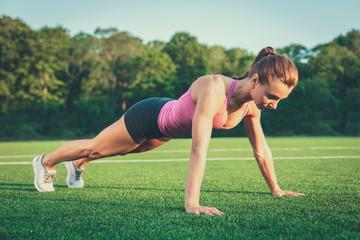 Woman doing push ups outdoor. Girl exercising