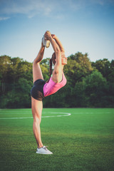 Healthy young woman practicing yoga outdoors. Woman doing sports