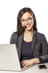 smiling girl working in the call center and posing on the desk