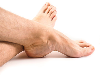 Hairy legs and feet of male person resting towards white backgro