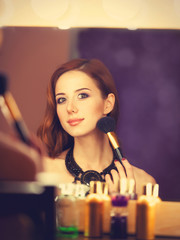 Beautiful redhead women appling makeup near mirror