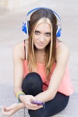 Beautiful casual woman listening to music with headphones and ph