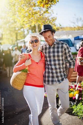 a young couple walking on a market on a sunny morning - 73803608