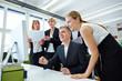 Team steht um Monitor mit Touchscreen im Büro