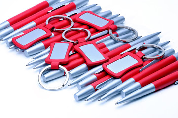 Silver-red metal pens and keychains isolated on white.