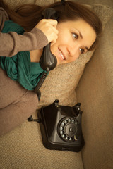Cheerful young woman making phone call on sofa