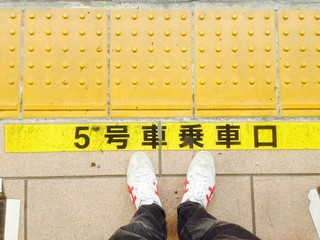 my feet behind the line at train station,japan