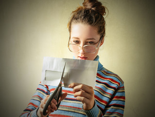 Girl carefully cutting an envelop