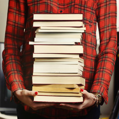 Woman holding a pile of books for studying concept.
