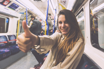 Happy Young Woman Commuting by Tube