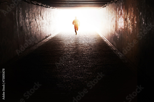 Man running through the tunnel in the sun - 73805678