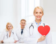 smiling female doctor with heart and stethoscope