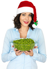 Young Woman in Santa Hat Holding a Bowl of Peas