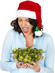 Young Woman in Santa Hat Holding a Bowl of Brussel Sprouts