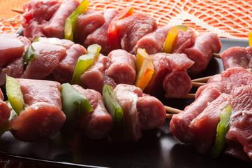 Spiedini di carne di vitello crudi su un piatto
