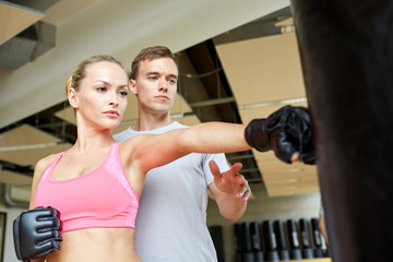 woman with personal trainer boxing in gym
