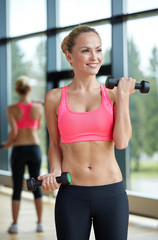 young sporty woman with dumbbells flexing biceps