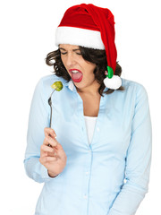 Young Woman in Santa Hat Eating a Brussel Sprout off a Fork