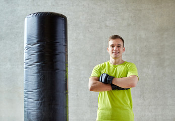 man with boxing gloves and punching bag in gym